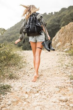 Young woman hiking barefoot up a rocky road, carrying a black backpack and leather boots.