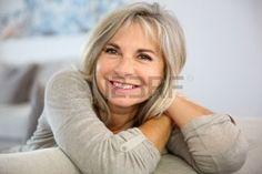 L�chelnde �ltere Frau sitzen in der Couch zu Hause photo