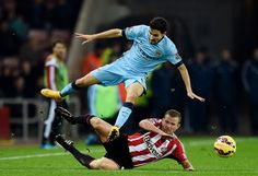 Jesus Navas of Manchester City is tackled by Lee Cattermole of Sunderland during the Barclays Premier League match between Sunderland and Manchester City at The Stadium of Light on December 3, 2014 in Sunderland, England.