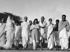 Gandhi takes his daily walk round his garden with his secretaries and members of his family in 1946.
