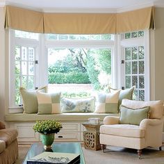 Change the focus of a room from the fireplace in winter to a beautiful window view in spring, rearranging the furnishings as needed. In this family room all eyes are on the window seat where a creamy yellow and green color palette frames the view. The scheme provides a light touch but a mix of textures—chenille, linen, damask, and wool—adds dimension./