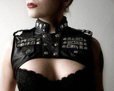 Lun dun gilet court genre fait de cuir véritable noir. Long frange, de chaînes, de goujons et de détresse partout. Boucles pour obtenir dans. Entièrement doublé.  Taille : Medium Buste 34-37(86-94cm) Mensurations : 18,5(47cm) de laisselle à aisselle le long du dos, 15(39cm) de la couture de lépaule à la couture dépaule 6,5(16cm) du col vers le bas le long du dos Frange jusquà 19(48cm)  Il sagit dun dun élément de la nature, le gilet que vous recevez est le même que ci-dessus. Cuir utilisé…