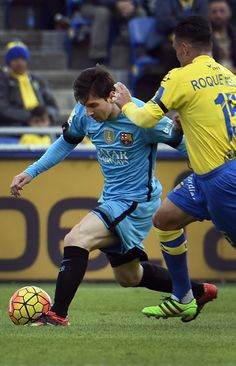 Barcelona's Argentinian forward Lionel Messi (L) vies with Las Palmas' midfielder Roque Mesa Quevedo during the Spanish league football match UD Las Palmas vs FC Barcelona at the Gran Canaria stadium in Las Palmas de Gran Canaria on February 20, 2016.