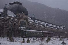 Vista exterior de la estación de Canfranc con dos vagones restaurados.