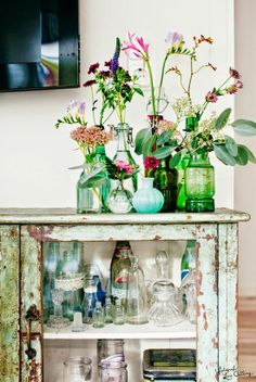 Love the chippy rustic cupboard and assortment of old glassware and bottles for vases!