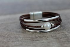 Sterling Silver Bracelet / Solitaire Pearl/ Simple Classic Chic One gorgeous solitaire 11-12 mm natural pearl is joined with two dainty sterling beads on each side and 2 sturdy sterling bars on multiple strands of Eco friendly leather that close with an European high quality magnetic