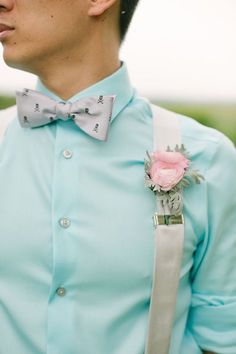Pale blue groom dress shirt with grey suspenders, a pink ranunculus boutonniere and indie skull bowtie @myweddingdotcom
