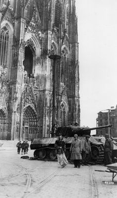 In Cologne, Germany, Kostelanetz and Pons posed in front of a burnt-out German tank and the Cathedral of Cologne, one of the few structures left standing after the Allies bombed the city.