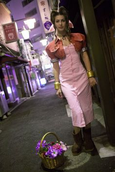 Aeris FF7 Costume. Pink dress, red short jacket, gold bracers, brown boots, pink bow, straight hair, basket of flowers.