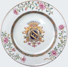 Paire d'assiettes à décor armorié pour le marché français en porcelaine de Chine d'époque Yongzheng. Compagnie des Indes. Porcelaine chinoise. Peintes dans les émaux de la famille rose, à décor sur le bassin des armoiries de la famille Bouczo du Rongoüet (Bretagne) : D'azur, à trois besants d'or, rangés en bande entre deux cotises de même. Sur le marli est peint une frise en or et grisailles, sur l'aile, trois delicates branches de pivoines.