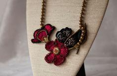 Rouge-bordeaux brodé fleur collier de déclaration, ancien bouton brodé, perles Noir dentelle, haute couture. Une combinaison de fleur en forme de tissu brodé et dentelle noire. Perles avec tchèque, cristal et perles plates.  Un bouton ancien brodé au milieu de la fleur rouge, ce qui en fait un bijoux éclectique.  Cette étole est la seule et l'existence seulement. C'est une œuvre d'art.  Le décolleté de perles en bronze mesure 15 cm de chaque côté et peut être adapté à n'importe quelle…