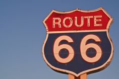 Red, white, and blue Route 66 neon sign at sunset