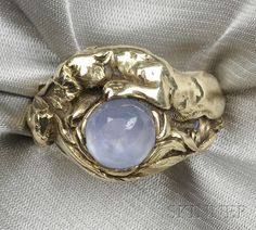 14kt Gold and Star Sapphire Ring, set with a cabochon star sapphire measuring approx. 8.28 x 8.00 x 4.83 mm, framed within a mount depicting a tiger confronting a snake, size 9 1/4. c. 1920s and attributed to Gustav Manz. A drawing for this design is in the collection of the Winterthur Museum.