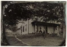 Anonymous | Bewoners voor hun houten huis, Anonymous, c. 1860 - c. 1900 | Houten huis, omzoomd door bomen, met de bewoners ervoor, onder wie een man met een zeis.