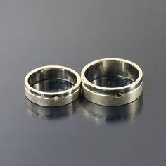 Obrączki z białego złota w dwóch fakturach: poler i szron. W damskiej wprawiono 2 białe brylanty, a w męskiej 2 czarne.