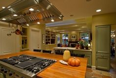 Eclectic Kitchen with Island Hood, can lights, Wood counters, Flat panel cabinets, Fireplace, stone tile floors, Paint 1  www.ShelbyLaneRewards.com  for CASH BACK at Home Depot, Lowes & More