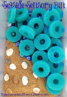 Seaside Sensory Bin with shells, sand, sliced pool noodles, blue foam bits, glass beads