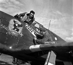 World War II, England, April 1944, USAAF Mustang Fighter Station of Ace Pilots, Pilot Captain Gentile watches as a colleague affixs stickers onto the side of his aeroplane, each one representing a raid carried out by that aircraft