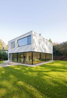Located on a secluded street in Schoten, the House G is a two-story near-cube white residence nicely integrated into the green surroundings.