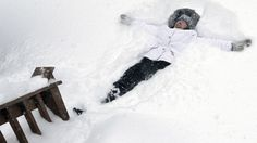 Nicole Lacoursiere of North Andover, Mass., falls back to make a snow angel in some 24 inches of snow that had fallen in her yard, Feb. 9, 2013. (AP Photo/Elise Amendola)