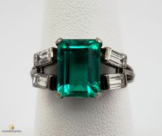 Gem green 2.30ct Emerald certified by the GIA to be of Columbian origin, mounted in a vintage 18kt white gold mounting with 4 straight baguette diamonds.