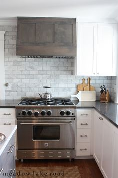Hood looks lost but like idea of mixing rustic wood with white kitchen-- Kitchen remodel featuring white shaker cabinets, gray quartz counters, custom gray range hood, marble subway tile backsplash White Shaker Cabinets, White Kitchen Cabinets, Kitchen Redo, Kitchen Tiles, New Kitchen, Kitchen Remodel, Kitchen Design, Gray Kitchen Backsplash, White Counters