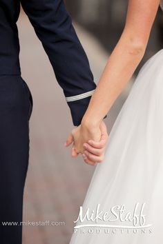 Love the bride and groom holding hands!