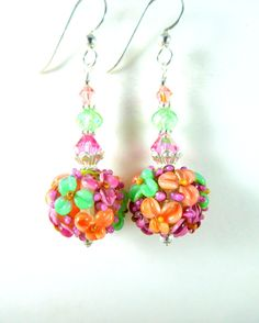 Handmade colorful Spring pastel floral earrings featuring pink, coral and mint green, purple, yellow floral artisan crafted lampwork beads; sterling silver; pink, green and peach Swarovski crystals. These gorgeous earrings are composed of beautifully detailed, 16mm round lampwork beads created by an SRA lampwork artist. The beads are clear with pink, coral and green flowers. Pink, green and peach Swarovski crystals compliment the beads and add sparkle. Sterling silver beads, bead caps…