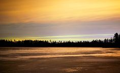 Frozen lake at night with sunset and orange colored sky and ice (Finland) by Teemu Tretjakov / 500px