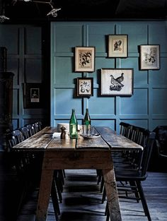 dark dining room with slate blue paneled walls, smoky blue, dusty blue, denim blue, french blue, pantone niagara, reclaimed wood dining table, black dining chairs, black and white wall art