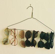 sweet home Wieso nicht einen guten Platz für Sonnenbrillen finden? Ganz einfach: Ein simpler Drahtkleiderbügel kann zum perfekten Platz für herumliegende Sonnenbrillen werden.
