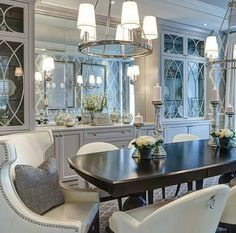 transitional dining room with Greek chairs, mirrored wall an white cabinets