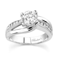 Feminine and graceful like the woman who wears this diamond engagement ring, featuring a white gold cathedral shank that splits and forms the prongs holding the round diamond center securely in place. Channel set diamonds cascade down the center ridge for an elegant touch of glam.<br /> <br /> Also available in rose/white gold, all  white or yellow gold, 18k and Platinum.