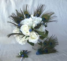 Bridal Bouquet - Hand wrapped bridal bouquet made with 9 peacock feathers, open and closed crème white roses, peacock blue glitter berries, and pearl sprays. I have partially wrapped the stems with white that is secured with pearl pins. The bouquet is 10 inches wide and 12 inches tall (Measuring from top of flowers to bottom of stems.) #timelesstreasure