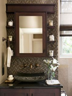 Designer Style - When cast-iron pipes within this bathroom¿s wall foiled plans for a wall-hung faucet, the wall behind the vanity was brought forward to make way for the plumbing valves. A dramatic mosaic backdrop provides a striking point of entry for the vanity. The dark-stained wood cabinetry and medicine cabinet present a clean-lined, sophisticated look.