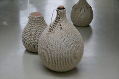 Glass bottles in knitted wool jackets with leather bottom, from Heins Home.