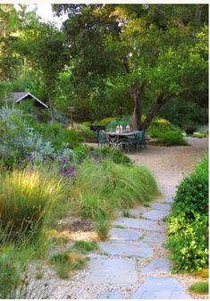 Mediterranean beauty: gravel patio with table and chairs, flagstone path, grassy, drought-tolerant garden. Bianchi Garden Santa Barbara, CA