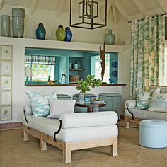Turquoise patterned curtains and pillows + a peek at the turquoise-painted kitchen beyond