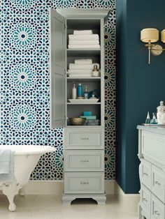 A vibrant paint color or patterned wallpaper paired with classic #cabinetry designs can add a touch of whimsy and elegance to your #bathroom. Note the light blue-gray tall linen bathroom cabinet. #OmegaVanityMakeover #contest