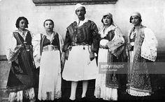 King Zog I of Albania (1895 - 1961), with his Queen Mother, centre left, and three of his sisters, all wearing Albanian national dress, circa 1935.