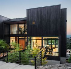 The exterior of the home is clad in black stained wood siding.