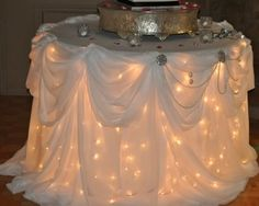 LOVE THIS IDEA! I could wrap one of the bistro tables outside on the patio with Christmas lights and then top it off with lace table cloths and broaches.