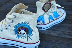 This pair of custom, hand painted white chuck taylor hi top converse sneakers features my tribal indian chief wearing a headdress. The Chief's headdress has blue feathers coming off the band that wrap