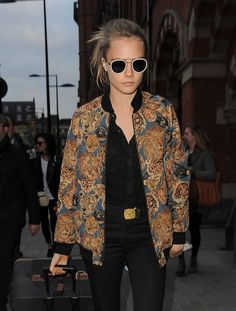 Cara Delevvigne sported a black button-down and pants, which she topped with a statement-making cat-print jacket and finished off with a cool pair of sunnies