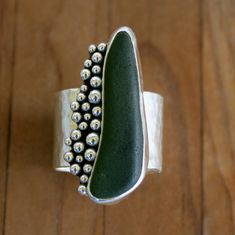 Kira Ferrer: Olive green sea glass wide band ring.