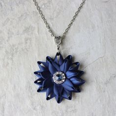 Your order will be shipped in 1-3 business days.   This flower necklace is handmade from satin ribbon in Navy Blue and features a sapphire blue and crystal center. Optional matching earrings can be purchased in the drop down menu above. All items ship are packaged in gift boxes with outer bow. The flower is 1 3/4 inches wide. The earrings have hypoallergenic posts (nickel-free) with butterfly backings. They are 1/2 wide (13mm). The removable pendant is shown on a chain set to the sh...