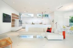 "Small bursts of color stand out starkly against the all-white palette of this modern, minimalist home. In the space, a combination of white and clear acrylic furnishings appear to ""float"" on the white floors. Even the baseboards are recessed to emphasize the home's feeling of weightlessness."