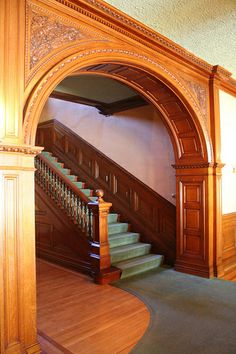 Heavy semicircular archways is a characteristic of Romanesque and Dichardsonian architecture. The staircase leads to the third floor. Note the intricate detailing of the spandrels. Wooden Door Design, Front Door Design, Staircase Handrail, Staircase Design, Victorian Interiors, Victorian Homes, J Hill, House On A Hill, Architectural Digest