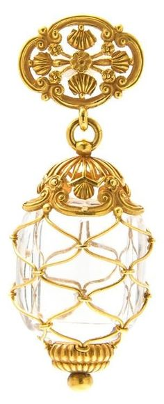 An Art Nouveau Yellow Gold and Rock Crystal Brooch, Tiffany & Co., consisting of a hollowed and polished rock crystal vessel within a gold wire netting setting capped at the terminals with fluted and scrolled openwork sections, suspended from a fluted openwork pin. Stamp: Tiffany & Co. #Tiffany #ArtNouveau #brooch