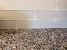 New Caledonia granite countertops and white glass tile backsplash.